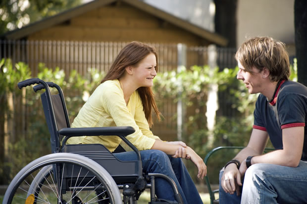 Disabled womain in wheelchair talking with man